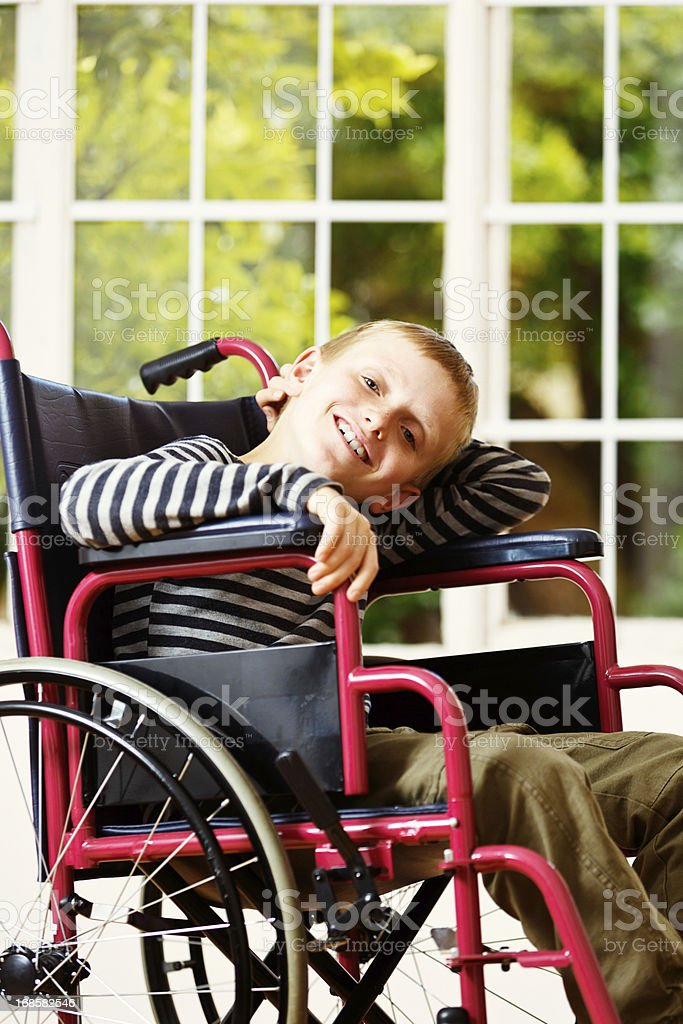 Disabled boy seems happy in his wheelchair stock photo