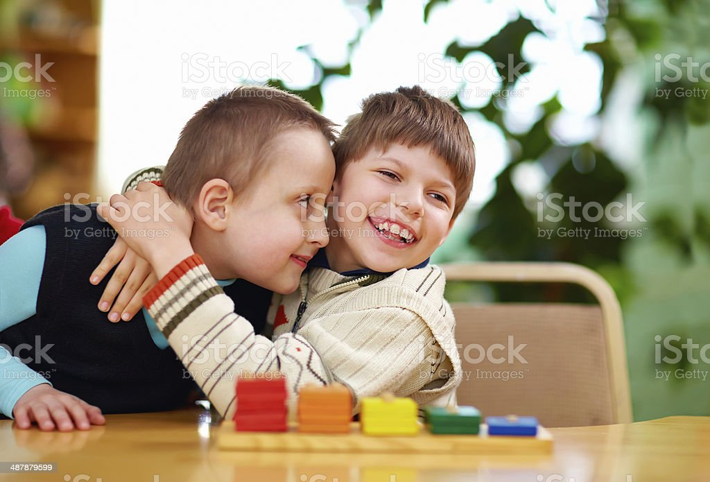 Disabled boys hugging happily in preschool stock photo