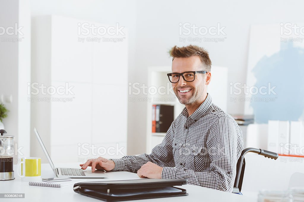 Disabled businessman working in an home office stock photo