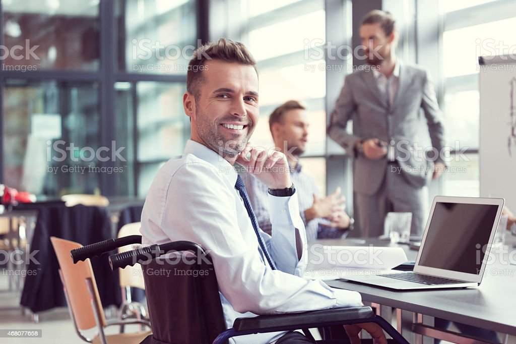 Disabled businessman working on computer in an office stock photo