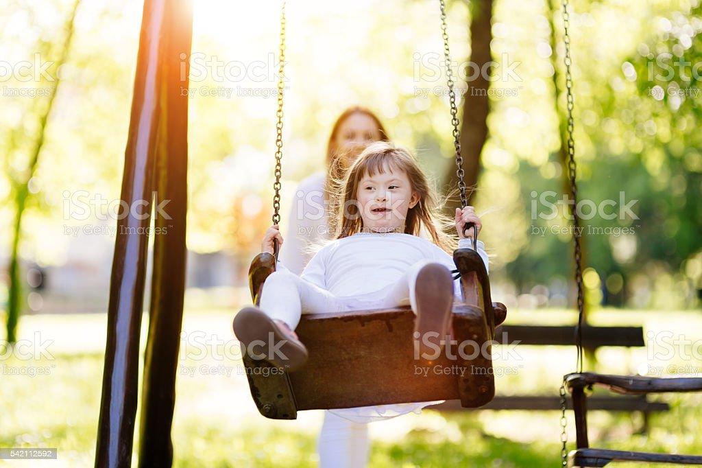 Disabled child enjoying the swing stock photo