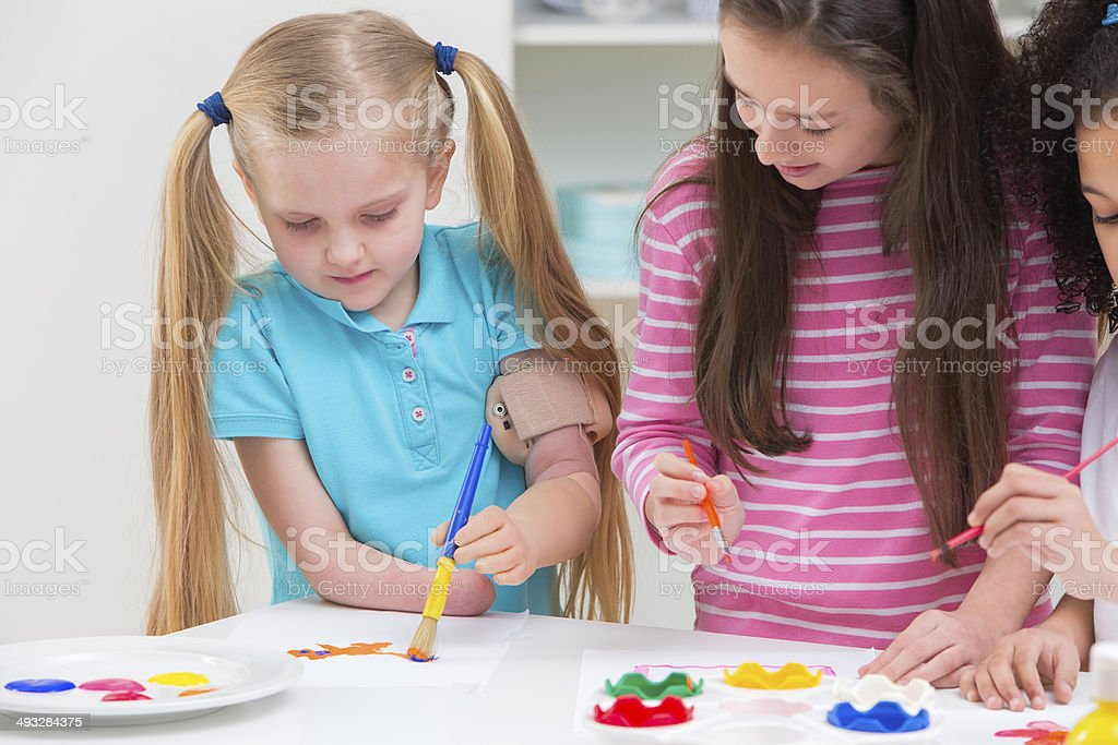 Disabled Child With Friends Painting Picture Together royalty-free stock photo