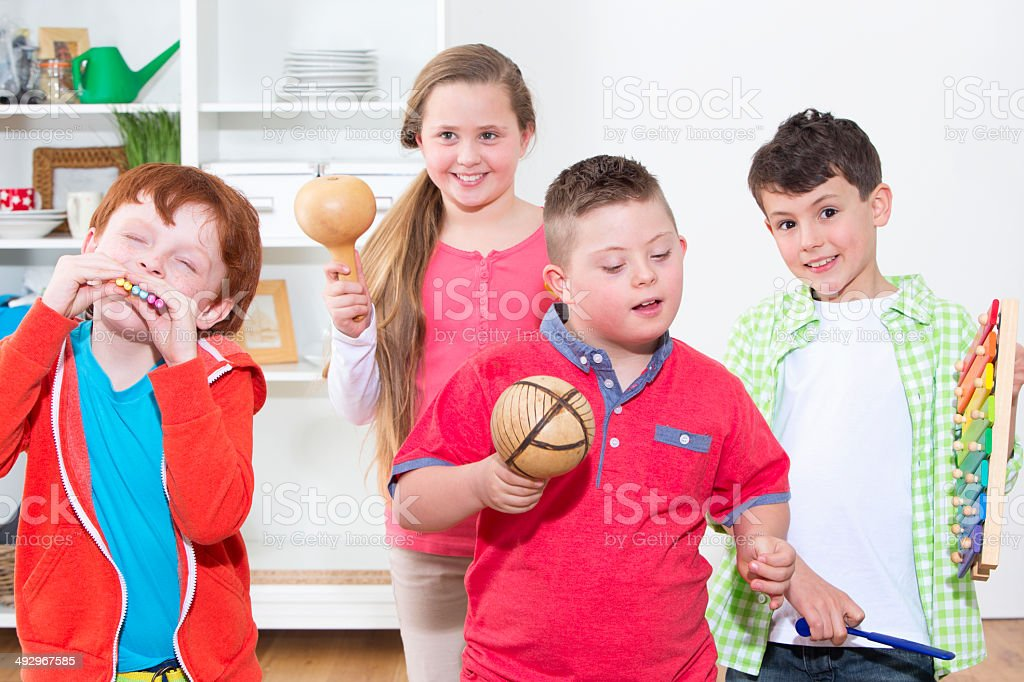 Disabled Child With Friends Playing Musical Instruments stock photo