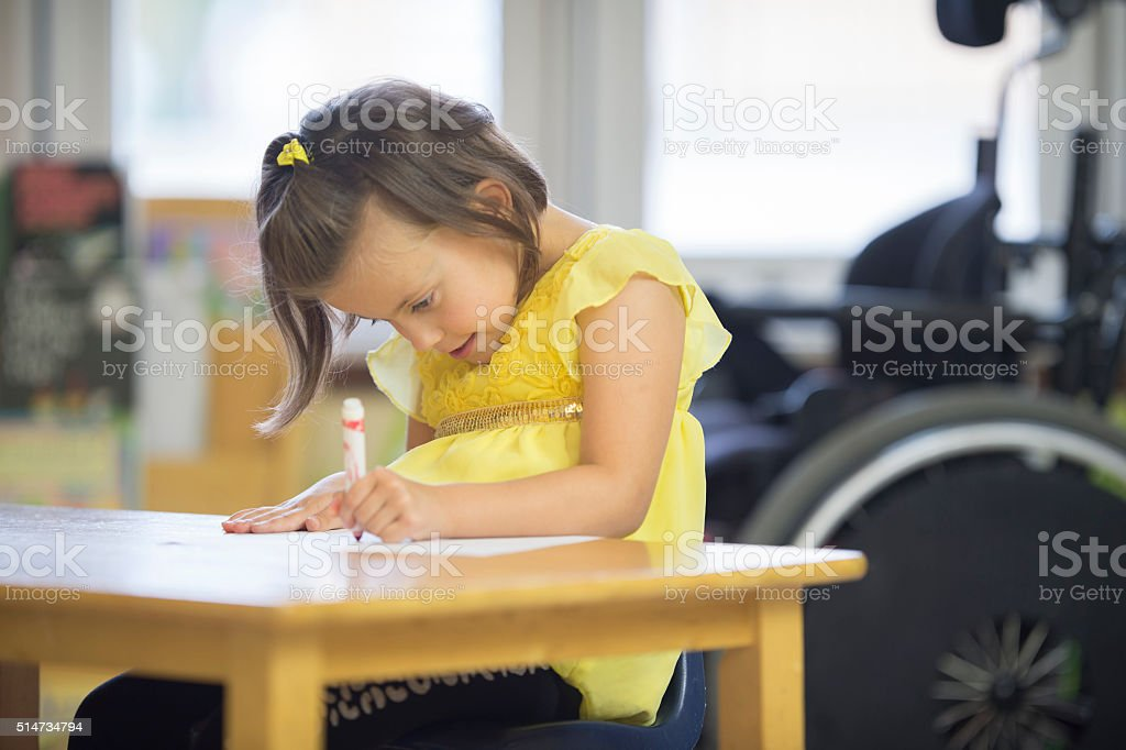 Disabled Girl Coloring at School stock photo