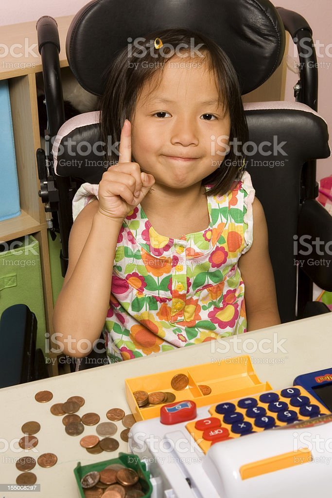 Disabled girl using toy cash register royalty-free stock photo