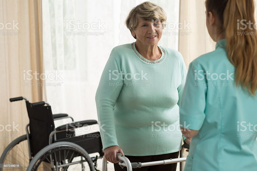 Disabled lady with a walking frame stock photo