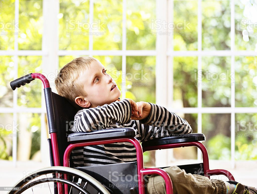 Disabled little boy in wheelchair looks up wistfully stock photo