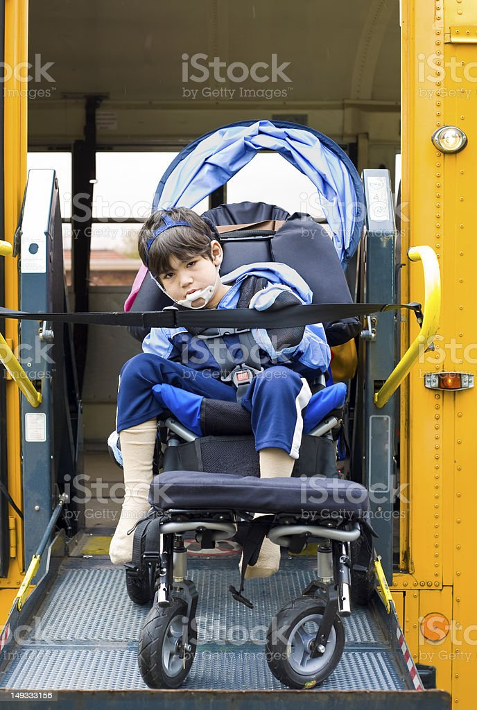 Disabled little boy on school bus wheelchair lift stock photo