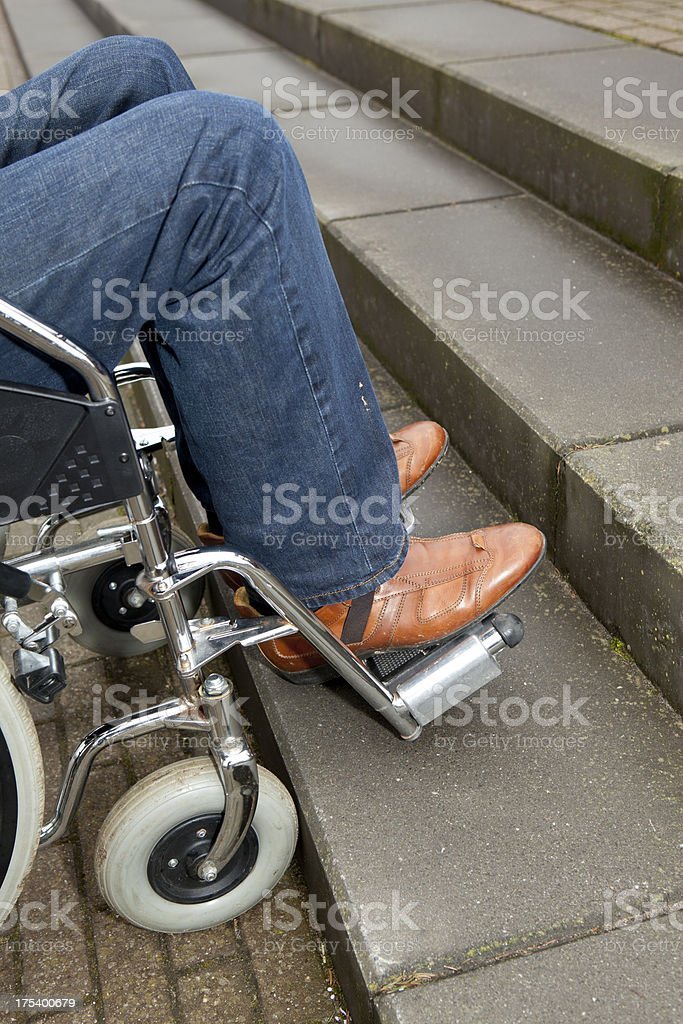Disabled Man at Foot of Stairs stock photo