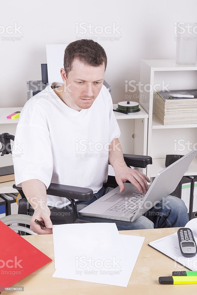disabled man in wheelchair at work royalty-free stock photo