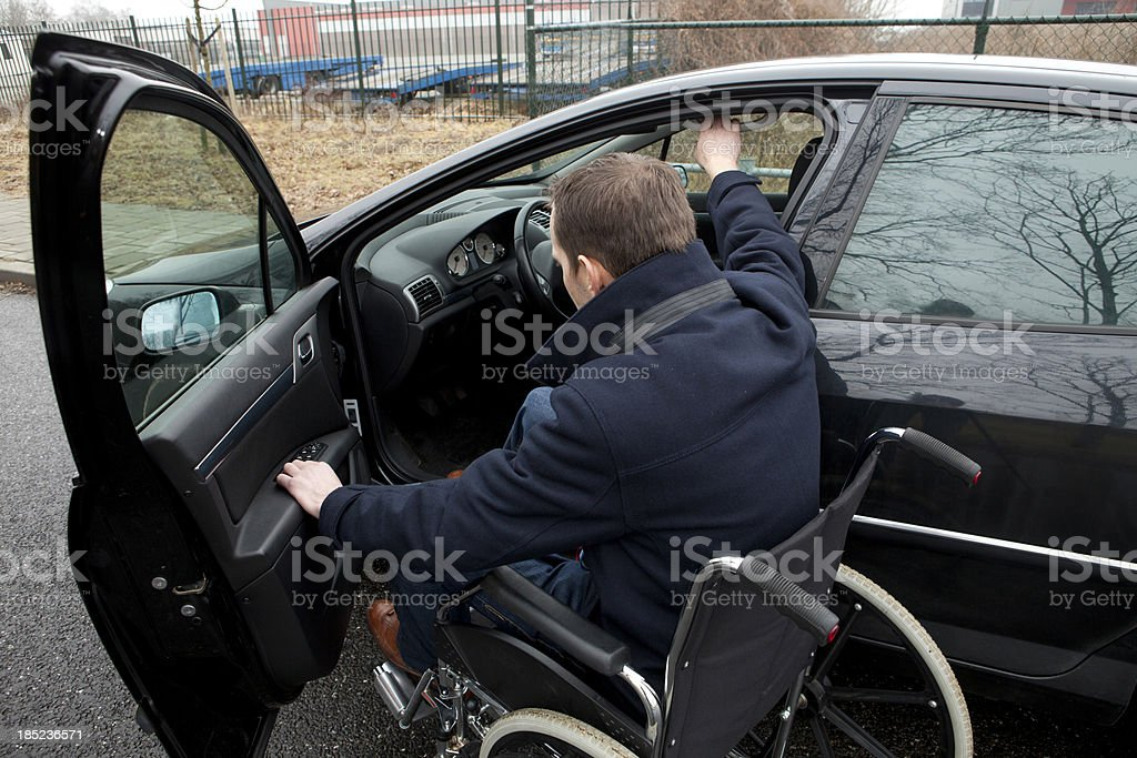 Disabled man in wheelchair get into car stock photo