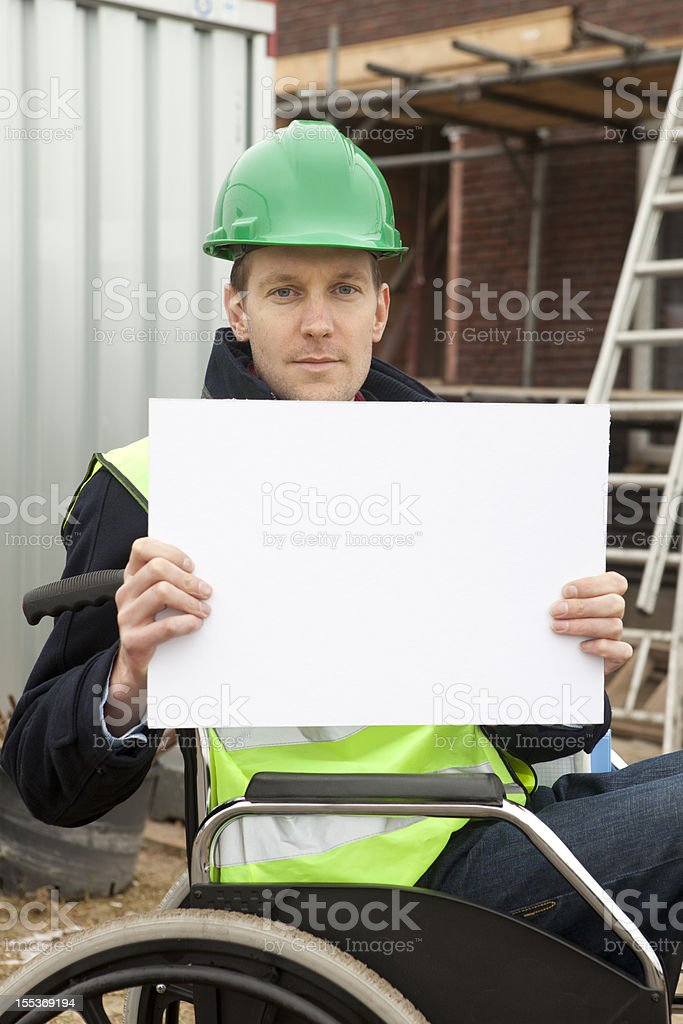 Disabled man in wheelchair holding billboard and looking at camera stock photo