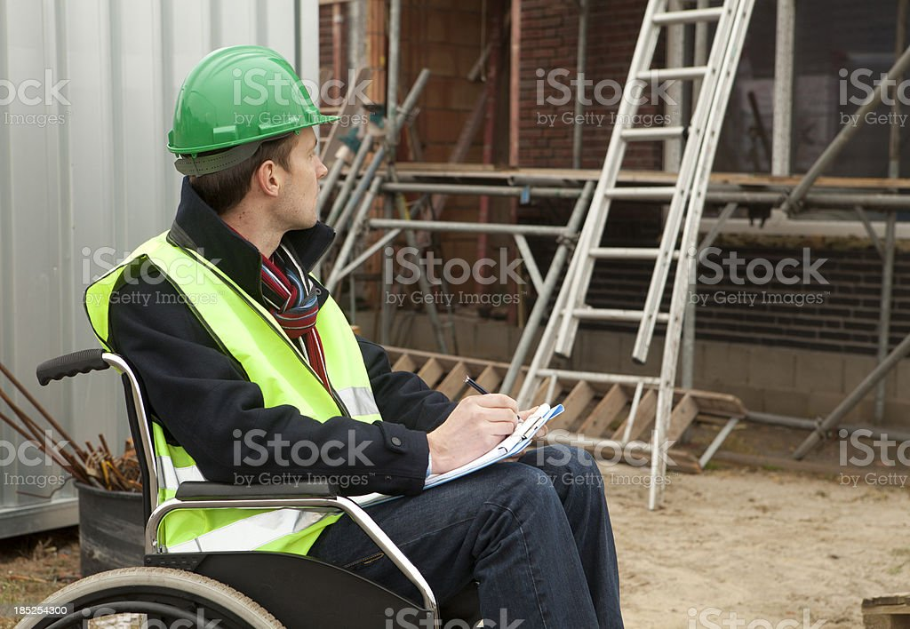 Disabled man in wheelchair looking at ladder after accident stock photo
