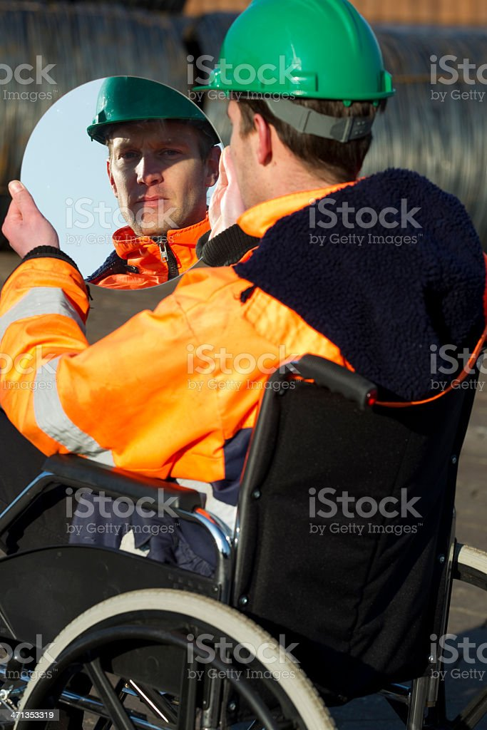 Disabled man in wheelchair looking at mirror stock photo