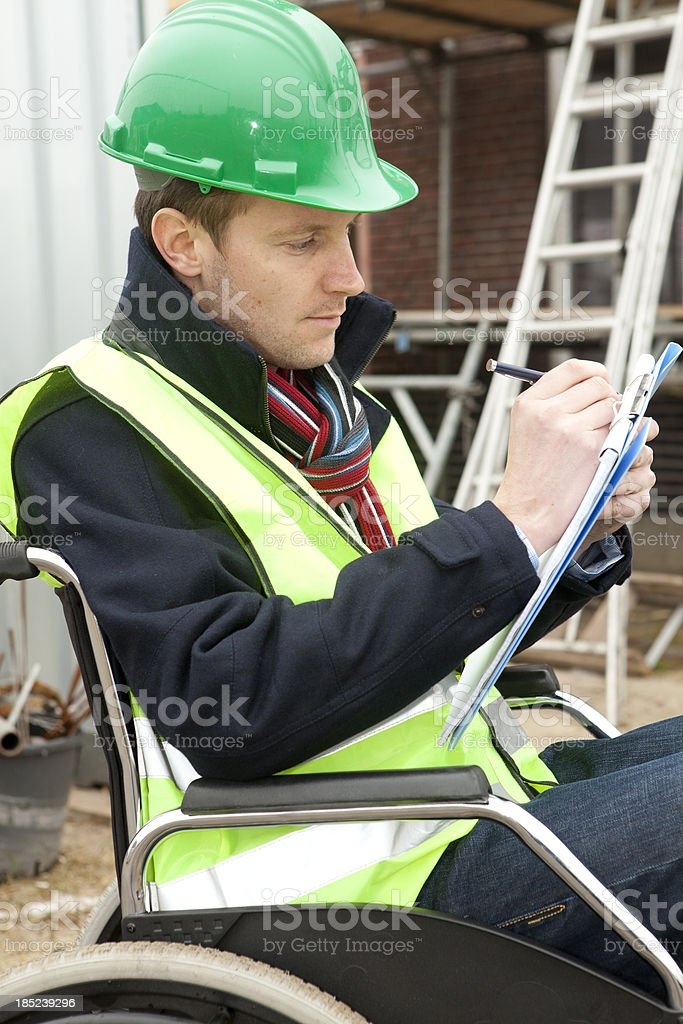 Disabled man in wheelchair working hard stock photo