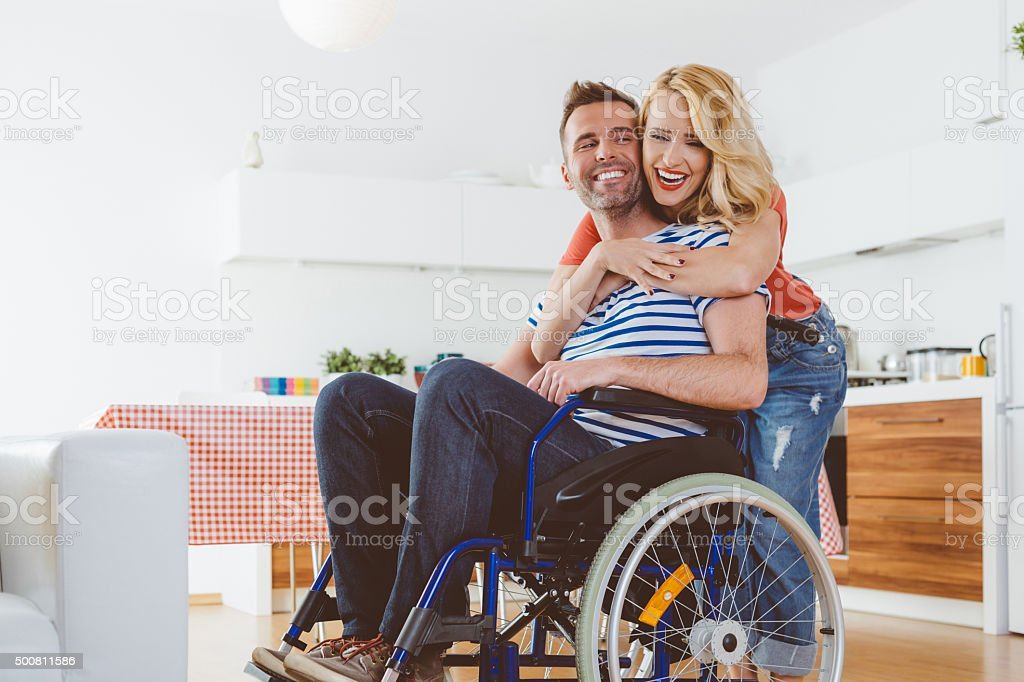 Disabled man sitting in a wheelchair, his wife embracing him stock photo