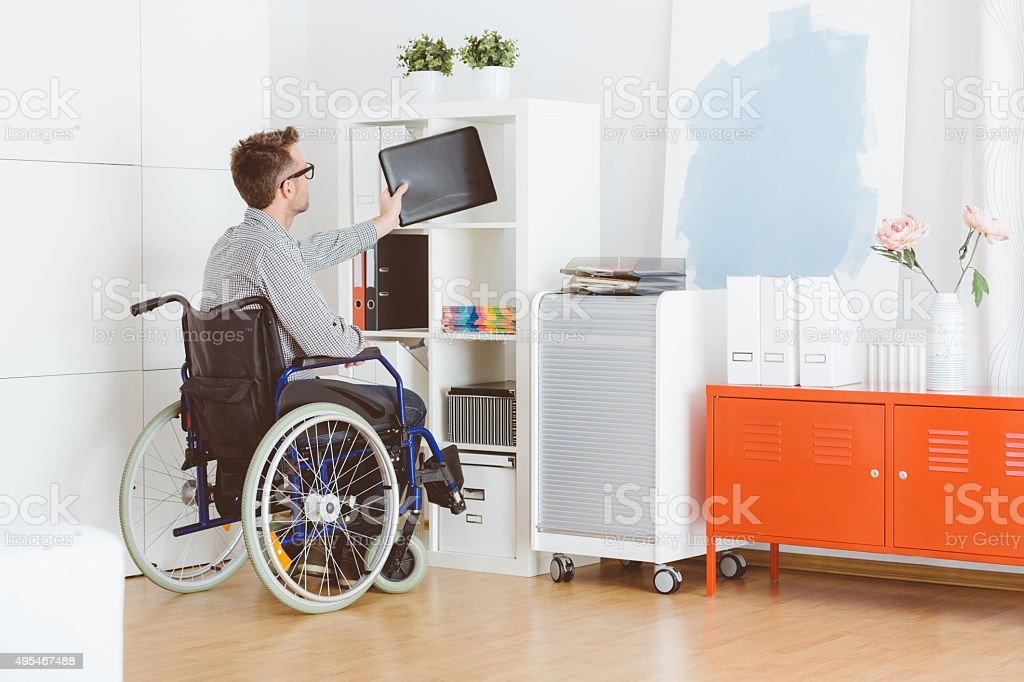 Disabled man sitting in a wheelchat at home stock photo