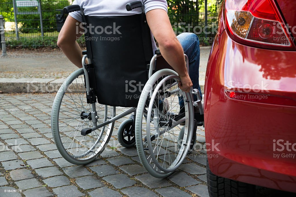 Disabled Man Sitting On A Wheelchair Near His Car stock photo