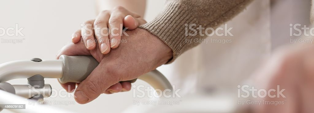 Disabled man walking with assistance stock photo
