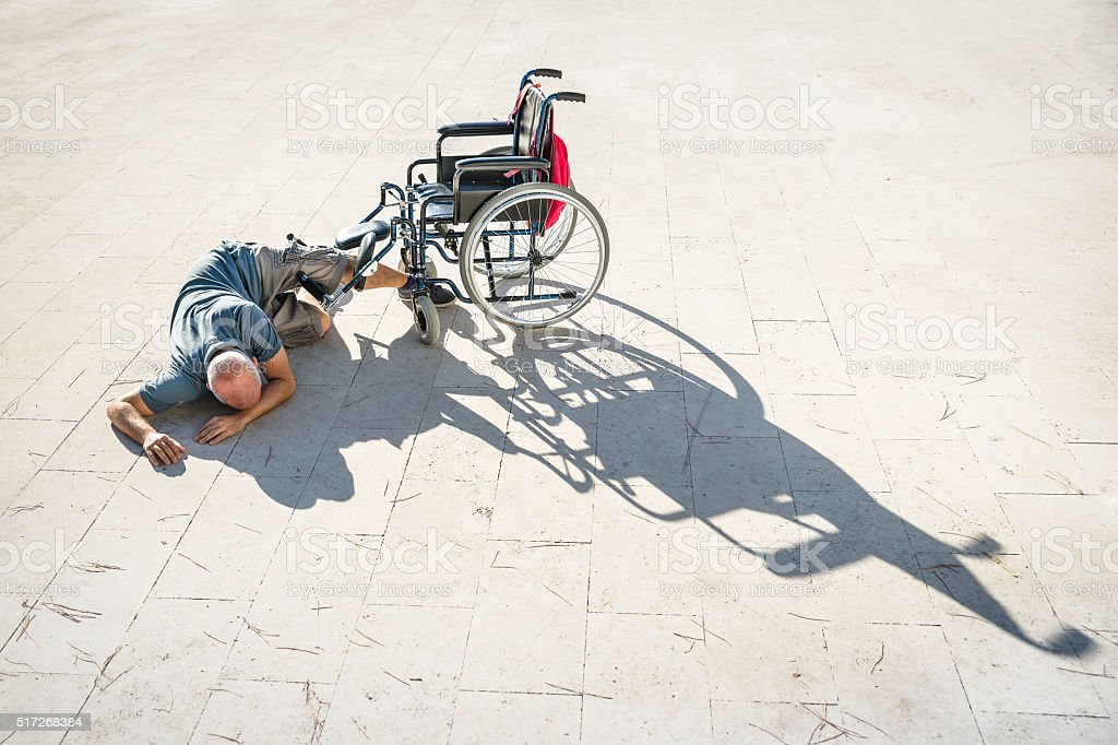 Disabled man with handicap having an accident crash with wheelchair stock photo