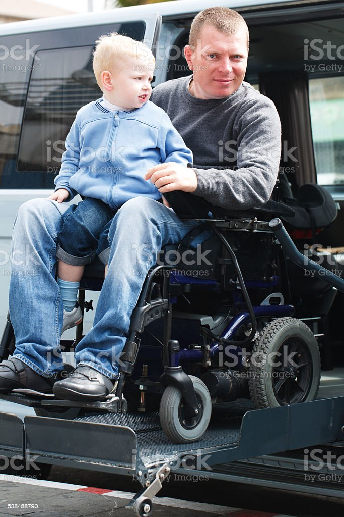 Disabled Men with son on Wheelchair Lift stock photo