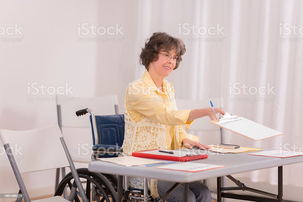 Disabled senior adult woman at conference or voter registration table. stock photo
