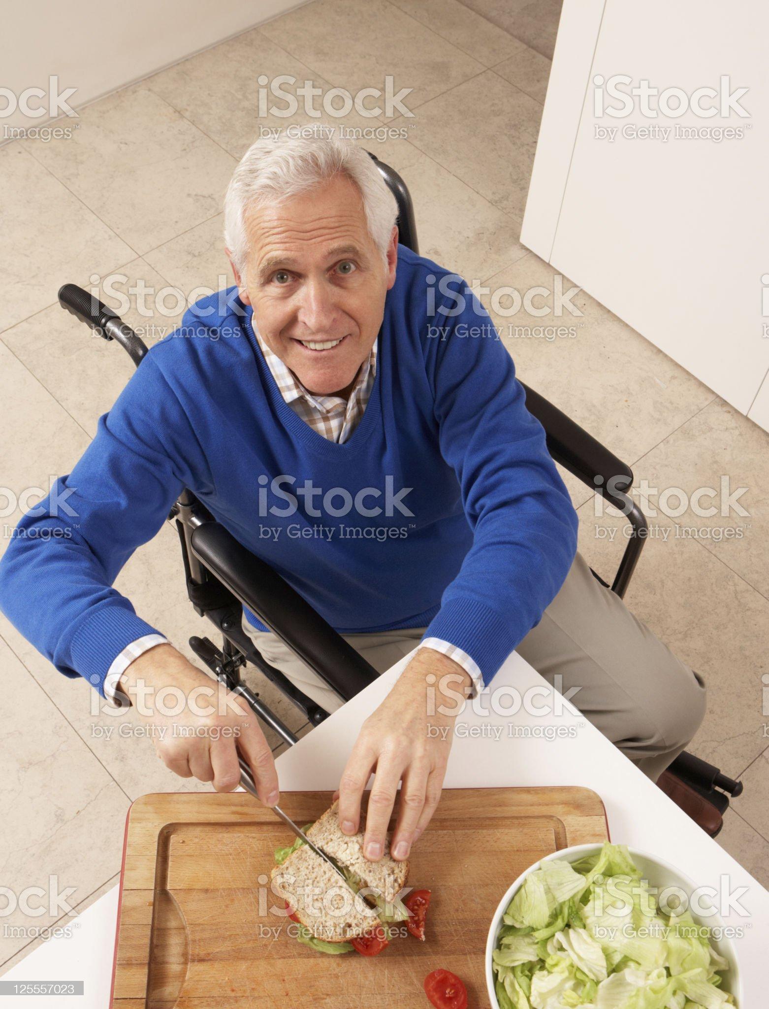 Disabled senior man cutting sandwich on cutting board royalty-free stock photo