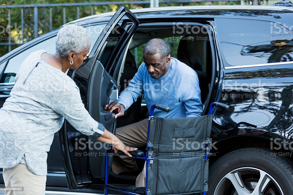 Disabled senior man getting from car to wheelchair stock photo