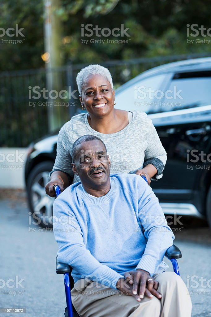 Disabled senior man in wheelchair with his devoted wife stock photo