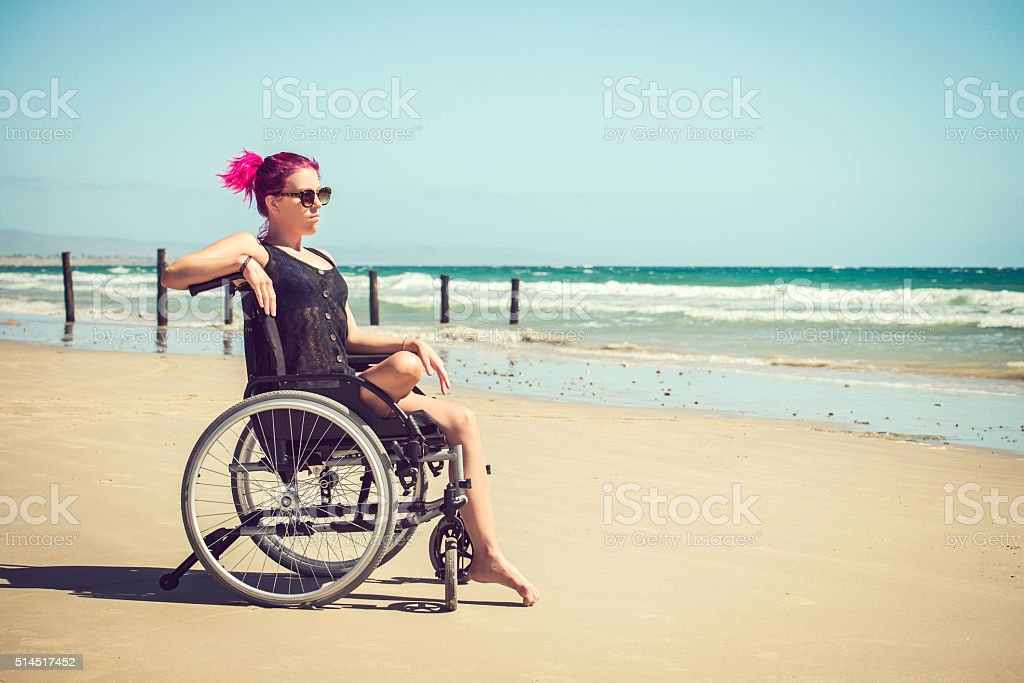 Disabled woman at the beach stock photo