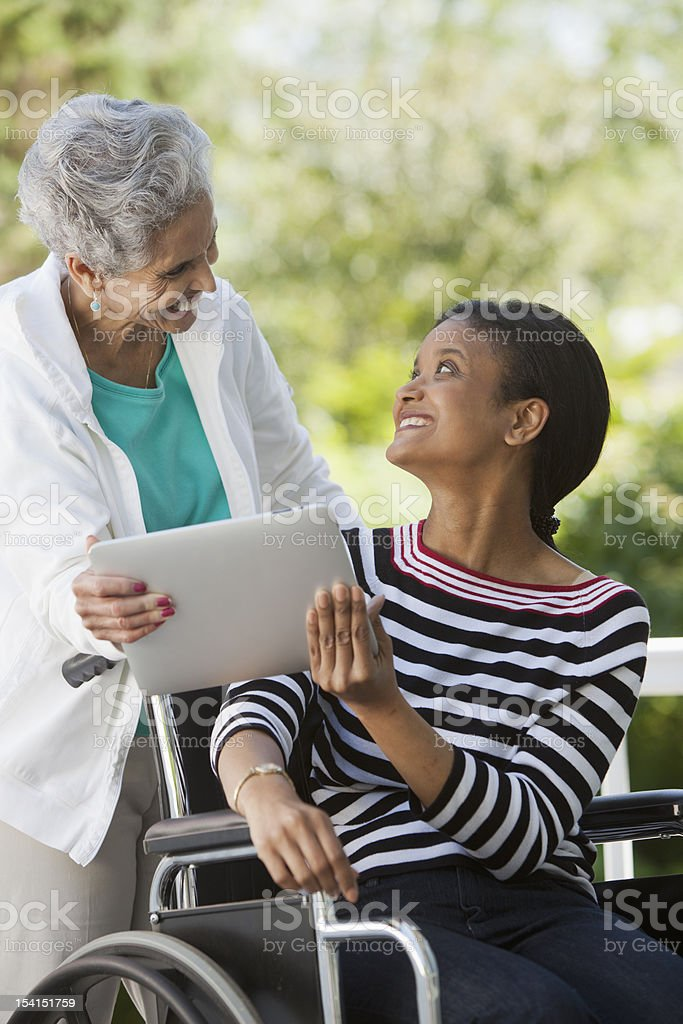Disabled woman in a wheelchair with her mother royalty-free stock photo