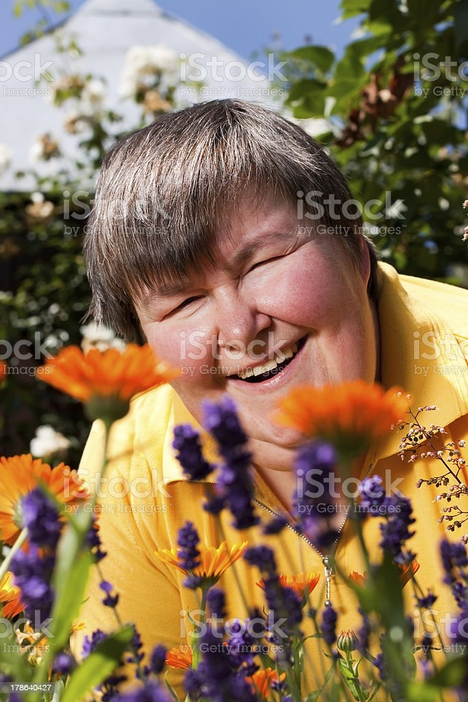 disabled woman lying in grass and smell on flowers royalty-free stock photo