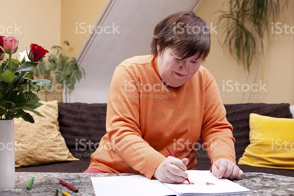 Disabled woman painted with pencils in a book royalty-free stock photo