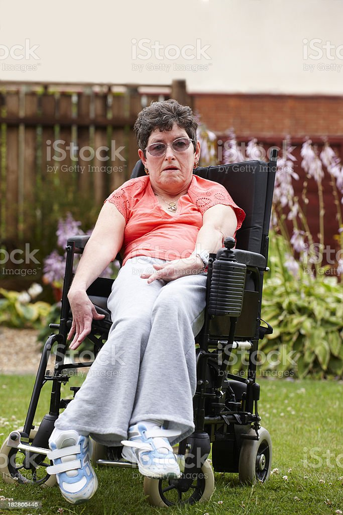 disabled woman sitting in wheelchair outdoors stock photo