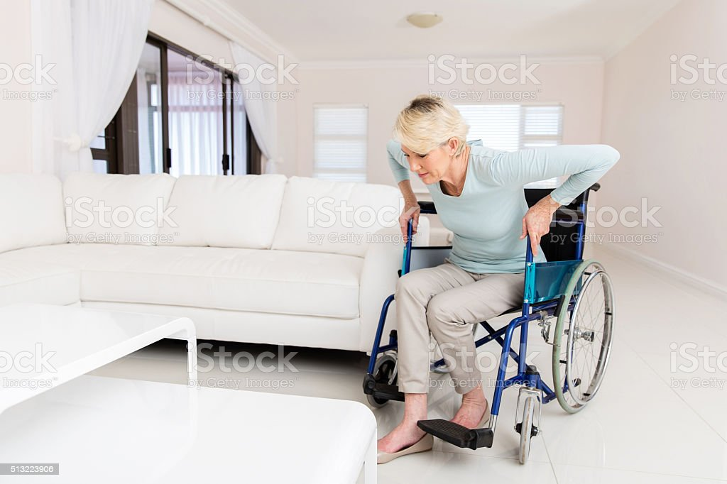 disabled woman trying to get up from wheelchair stock photo