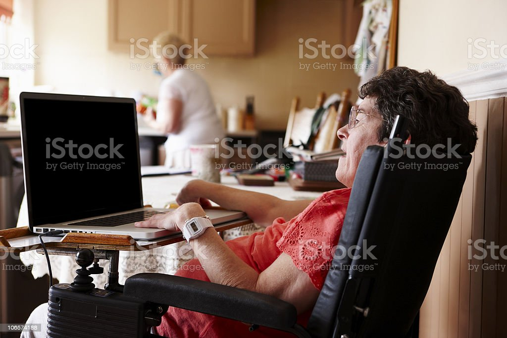 Disabled woman with hands on a laptop keyboard stock photo