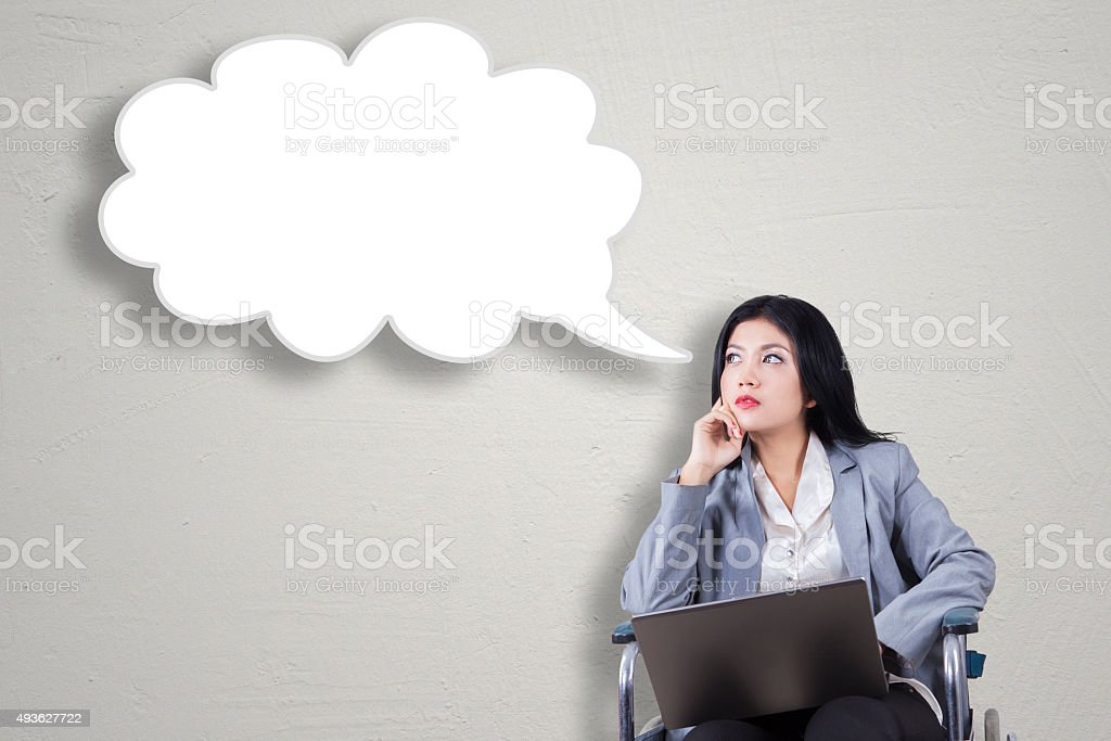 Disabled woman with laptop looking at speech bubble stock photo