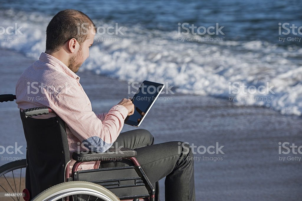 Disabled young man using touchpad royalty-free stock photo