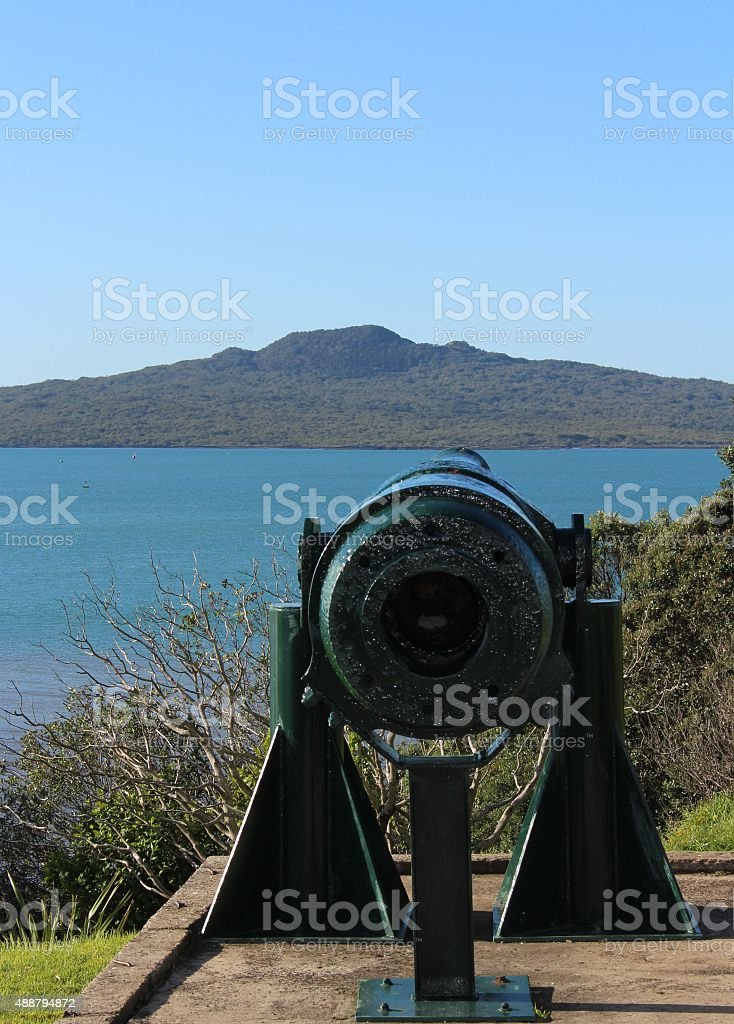 Disappearing gun pointing out to sea stock photo