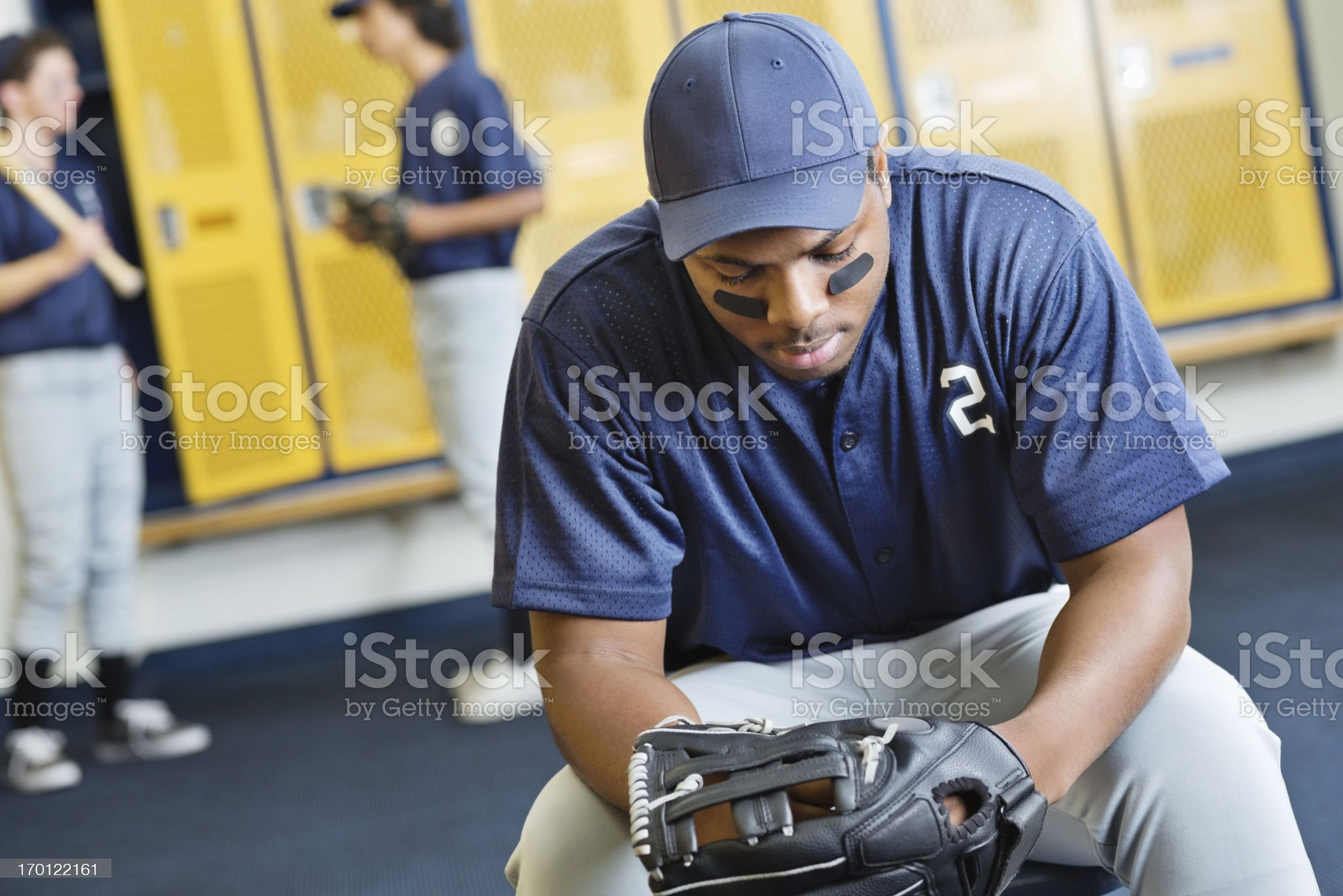 Disappointed baseball player in high school locker room royalty-free stock photo