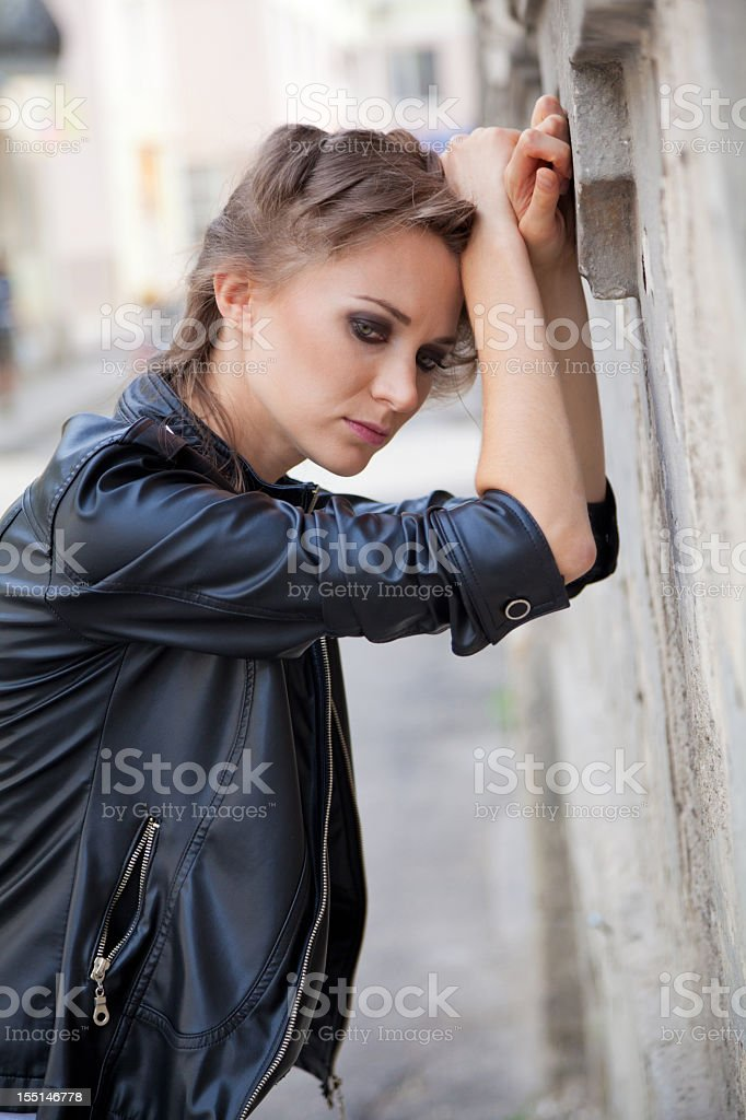 Disappointed  beautiful young woman leaning on building facade royalty-free stock photo