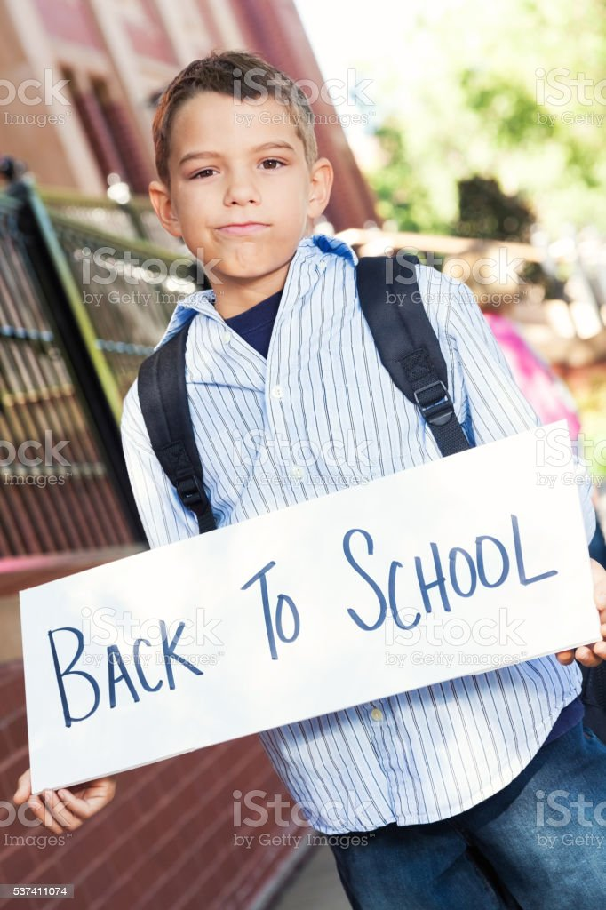 Disappointed boy holds 'back to school' sign stock photo