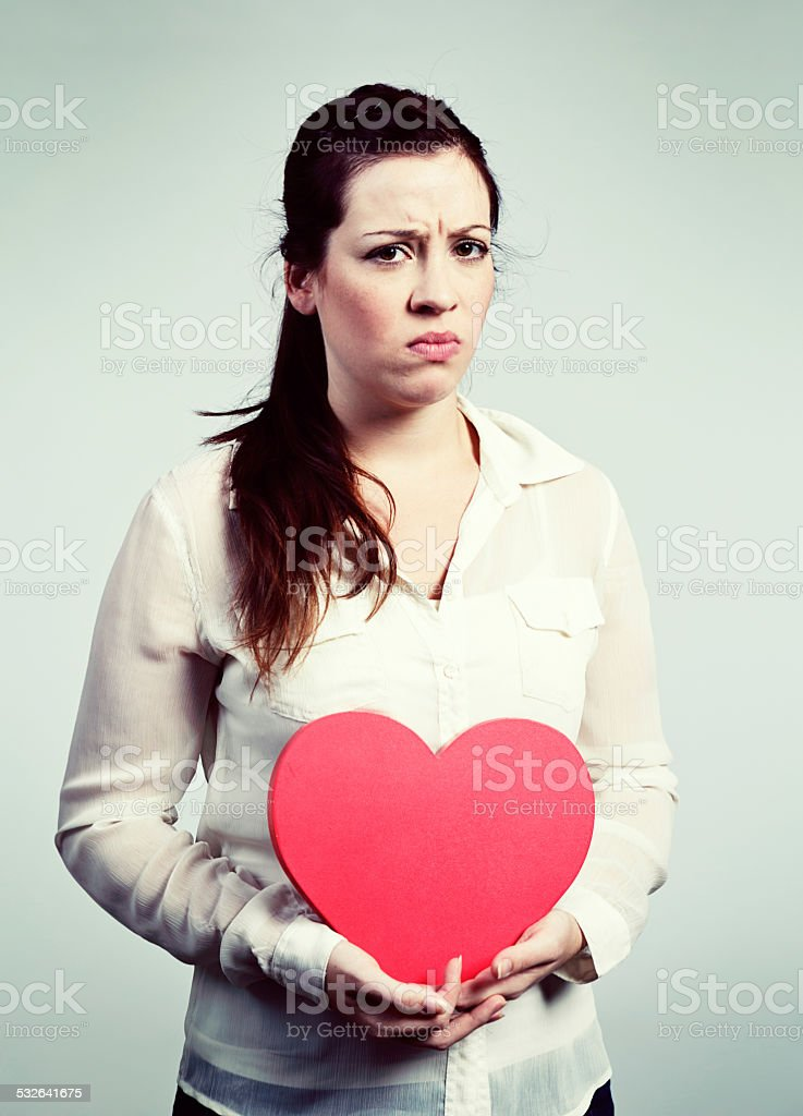 Disappointed brunette holds Valentine heart, frowning and frustrated stock photo