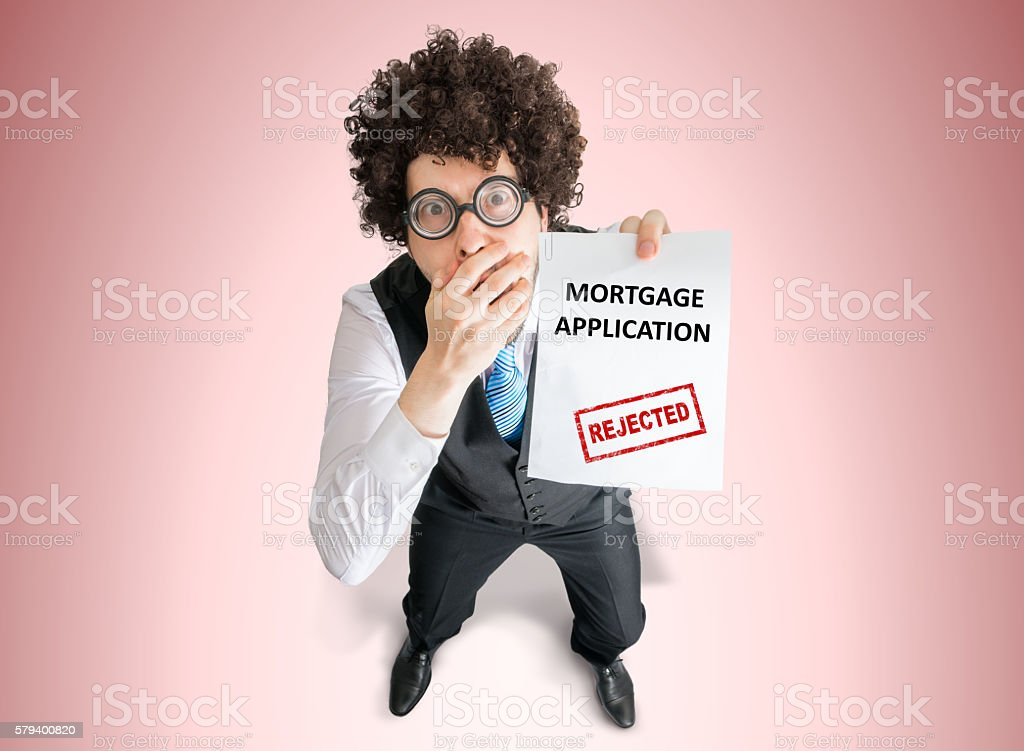 Disappointed businessman is showing document with denied mortgag stock photo