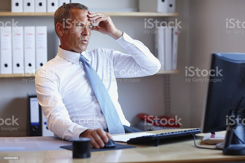 Disappointed businessman looking at computer screen royalty-free stock photo