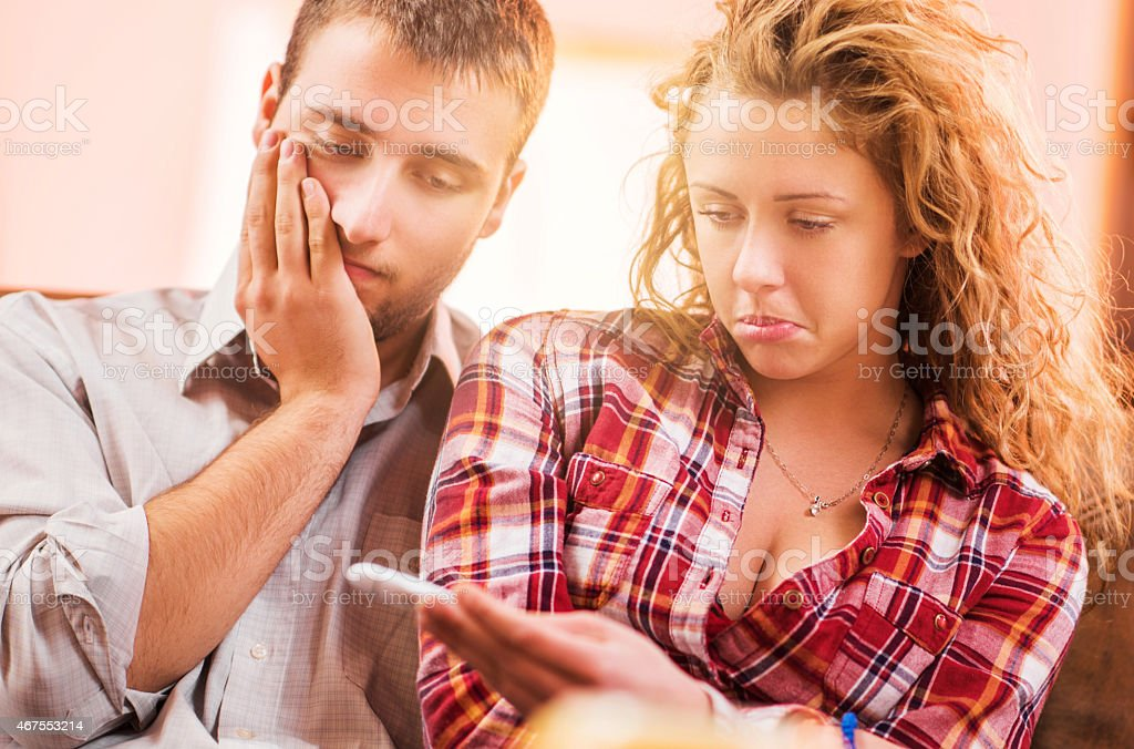 Disappointed couple looking at pregnancy test. stock photo