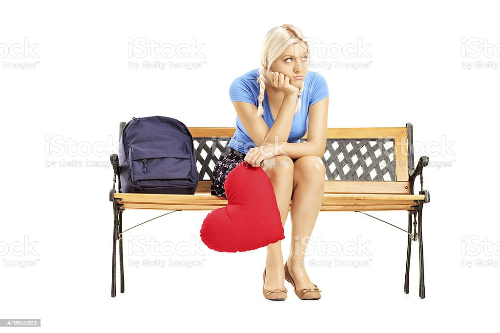 Disappointed female sitting on bench and holding a red heart royalty-free stock photo