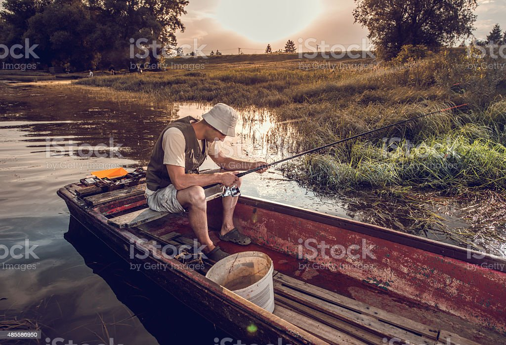 Disappointed fisherman in a boat on a river. stock photo