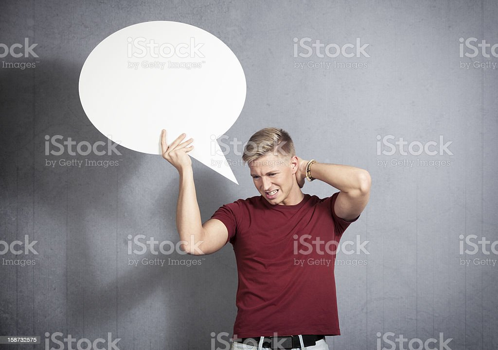 Disappointed man holding white blank speech balloon. royalty-free stock photo