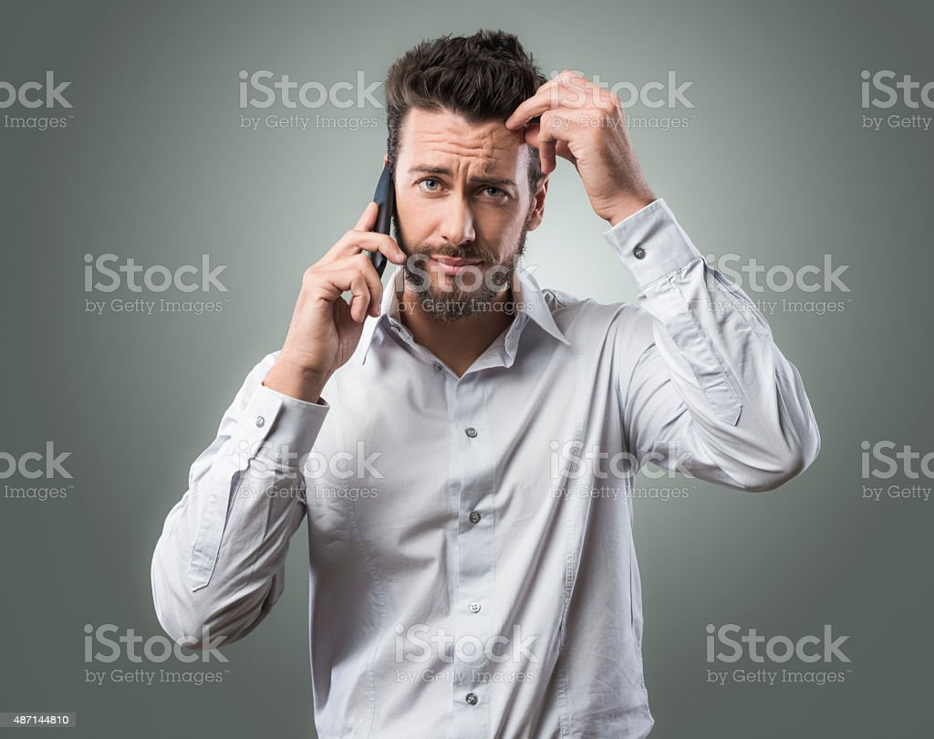 Disappointed man on the phone stock photo